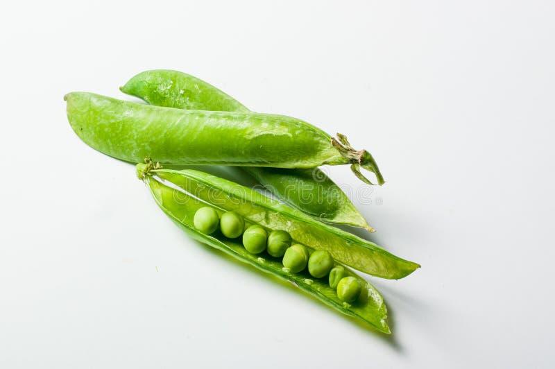 Frische grüne Erbsen auf weißem Hintergrund stockbilder