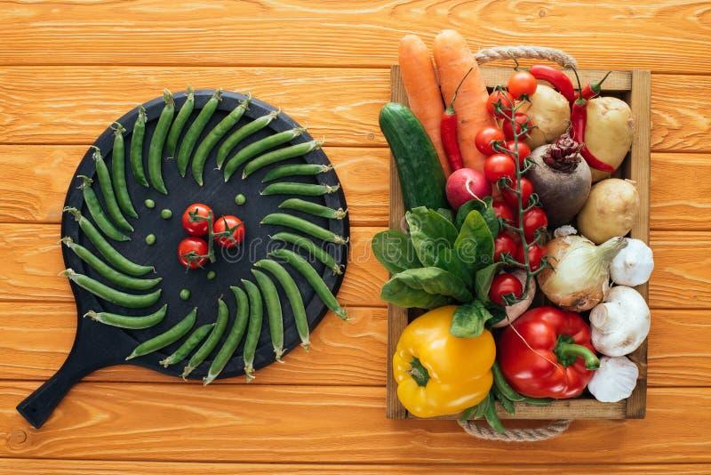 frische grüne Erbsen und Tomaten auf rundem Brett und rohes gesundes Gemüse im Kasten auf Holztisch stockfotografie
