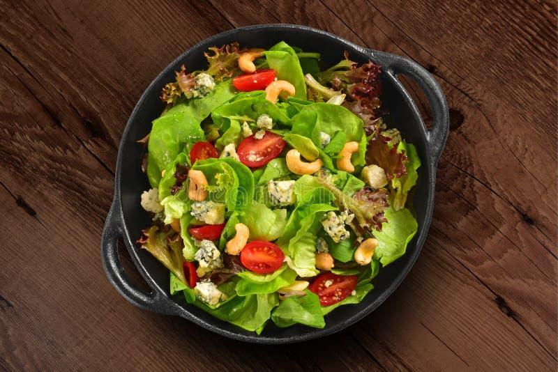 Frische grüne Salatpfanne isoliert auf Holzboden stockbild
