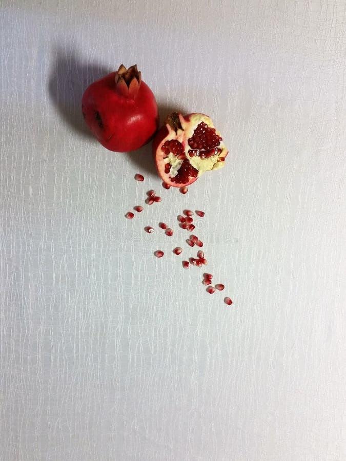 Frische Granatäpfel und Granatapfel-Bohnen auf einer festlichen weißen Tischdecke - ein Blick von oben stockfotografie