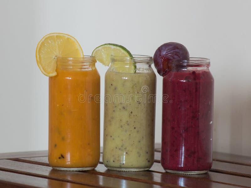 Frische Himbeere, Banane, Spinat und Orangensaftgetränke auf Holztisch stockbilder
