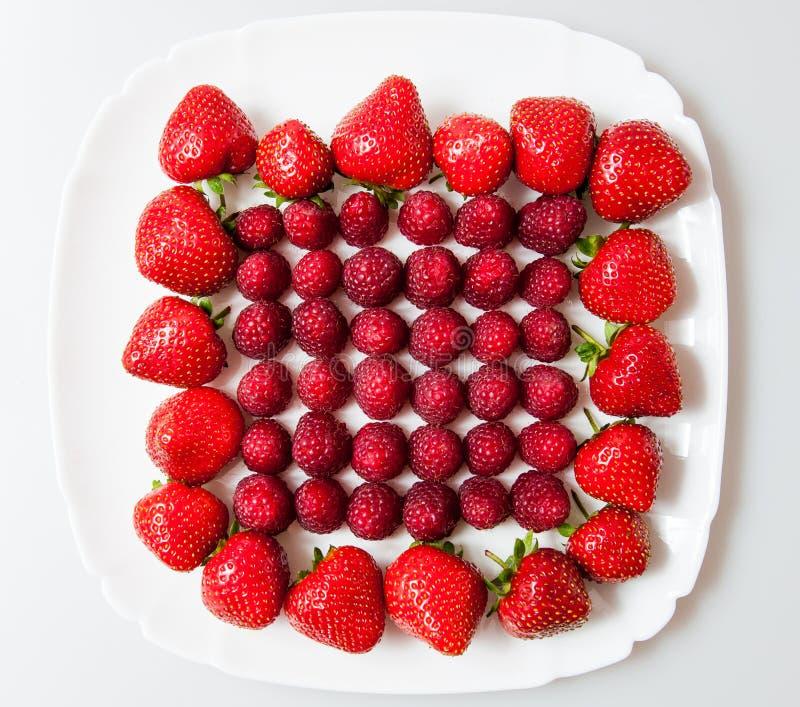 Frische Himbeeren und Erdbeeren auf einer weißen Platte lizenzfreie stockbilder