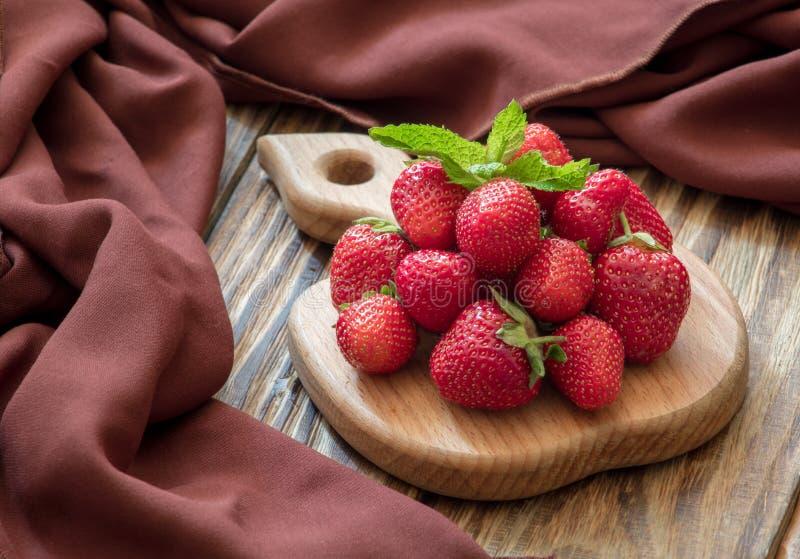Frische, köstliche Erdbeeren auf Holzbrett lizenzfreie stockbilder