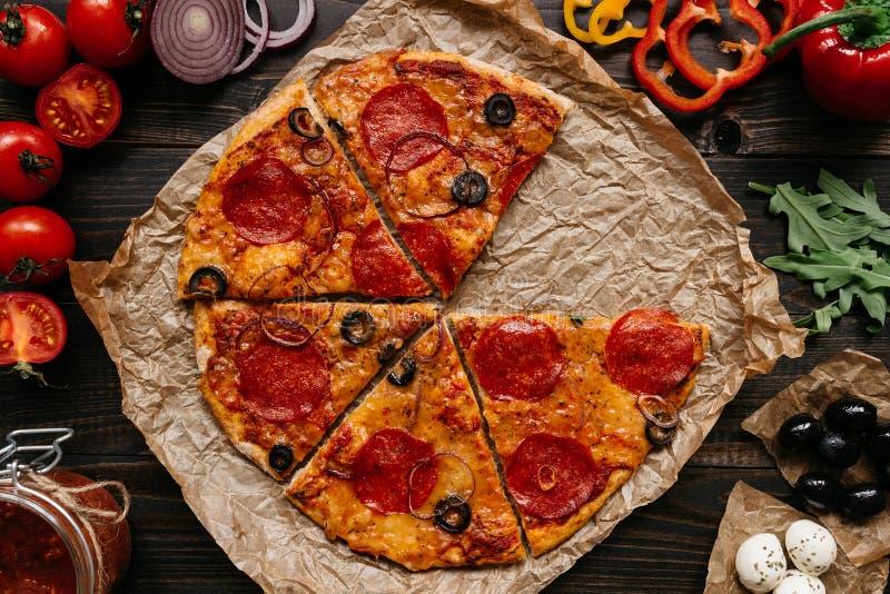 Frische köstliche Pizza mit Pizzabestandteilen auf dem Holztisch, Draufsicht lizenzfreies stockbild