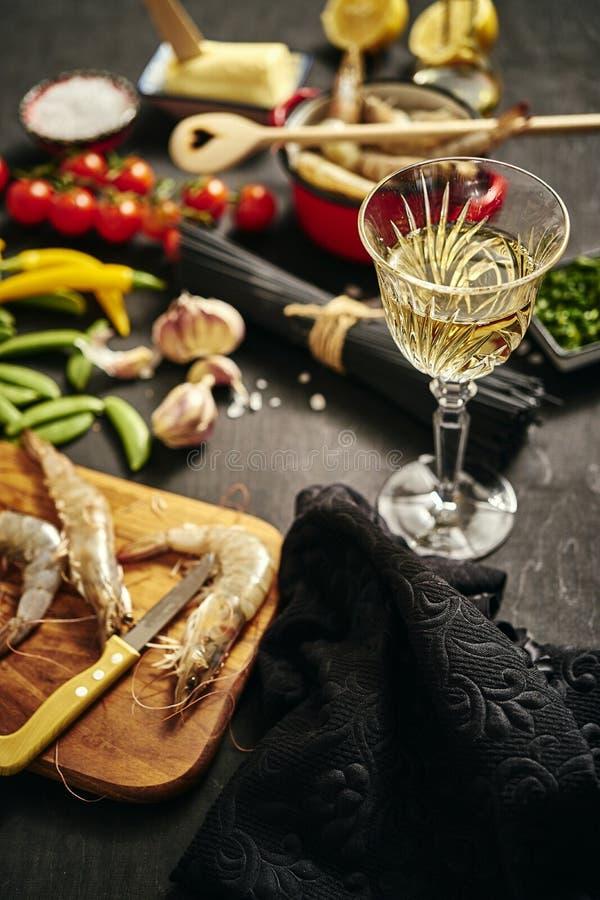 Frische köstliche rohe Tigergarnelen in einem Topf mit Petersilie, Zitrone, Butter, Tomaten und Paprika und Wein stockbilder