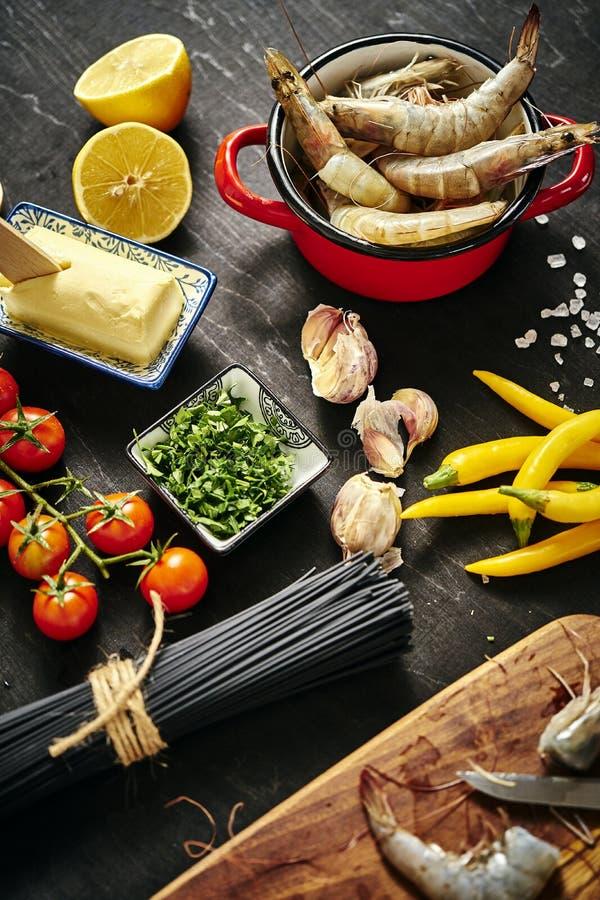 Frische köstliche rohe Tigergarnelen in einem Topf mit Petersilie, Zitrone, Butter, Tomaten und Paprikapfeffern stockfotos