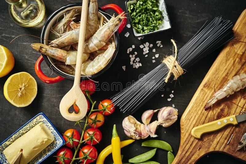 Frische köstliche rohe Tigergarnelen in einem Topf mit Petersilie, Zitrone, Butter, Tomaten und Paprikapfeffern stockfoto