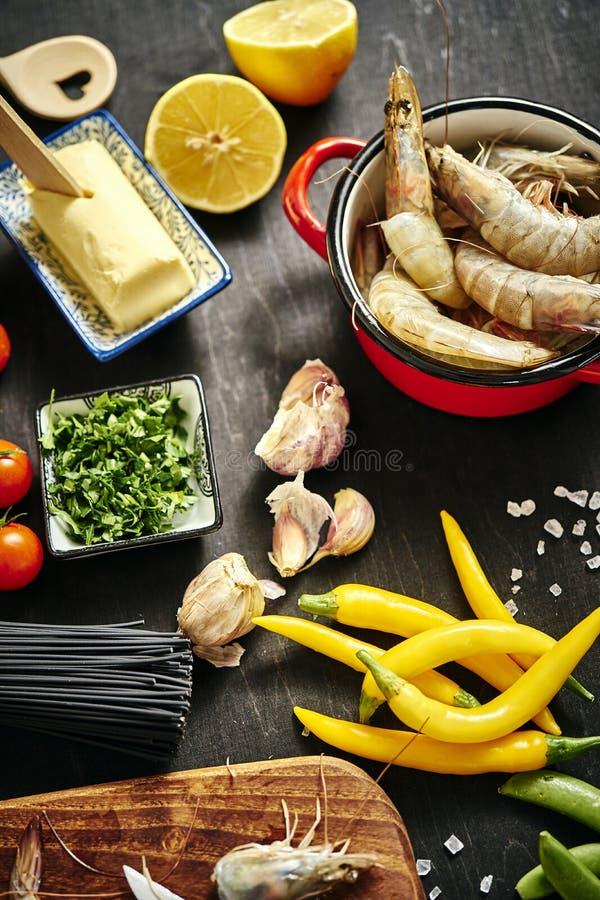 Frische köstliche rohe Tigergarnelen in einem Topf mit Petersilie, Zitrone, Butter, Tomaten und Paprikapfeffern lizenzfreie stockfotografie