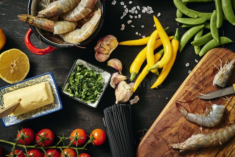Frische köstliche rohe Tigergarnelen in einem Topf mit Petersilie, Zitrone, Butter, Tomaten und Paprikapfeffern stockbild