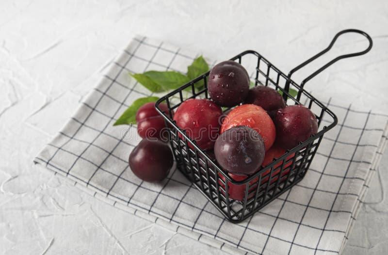 Frische köstliche rote Pflaumen Weet auf Tabellen-Sommerfrüchten des schwarzen Korbes weißen hölzernen lizenzfreies stockbild
