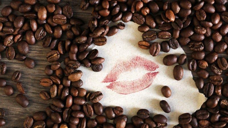Frische Kaffeebohnen und Lippenstiftlippen, Kuss lizenzfreies stockfoto