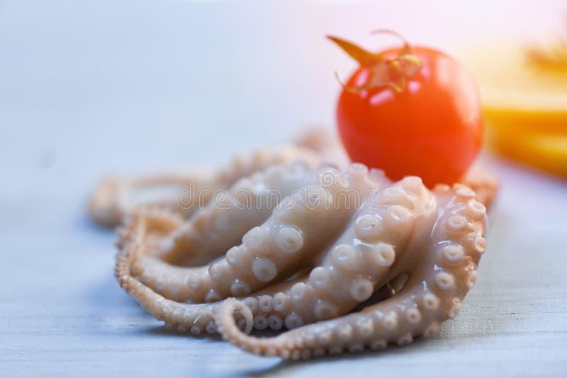 Frische Kalmarkrake der Meeresfrüchte roh und weißer hölzerner Hintergrund der Tomate stockbilder