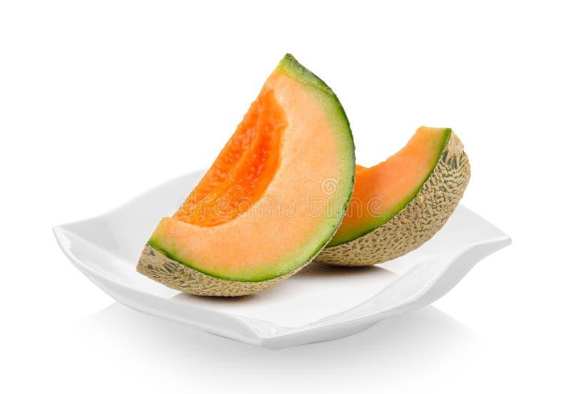 Frische Kantalupenmelone in der keramischen Platte auf weißem Hintergrund stockfotografie
