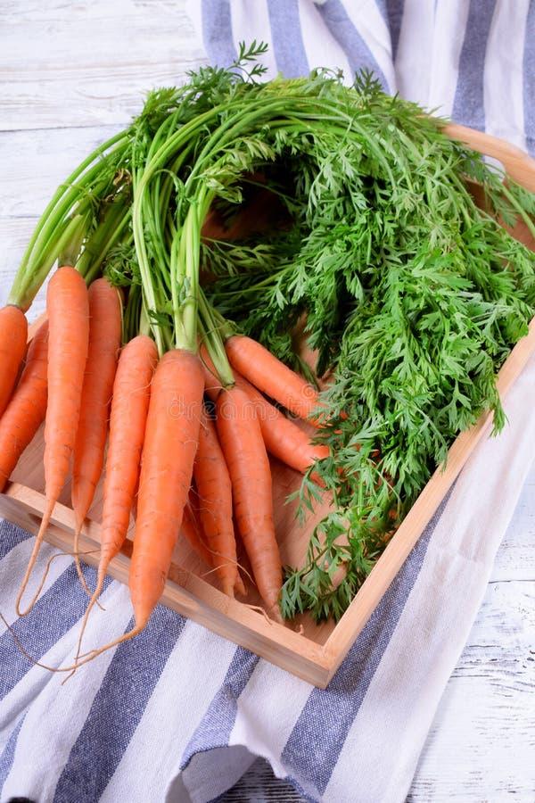 Frische Karotten mit grünen Spitzen in einem Kasten auf dem weißen hölzernen Hintergrund lizenzfreies stockbild