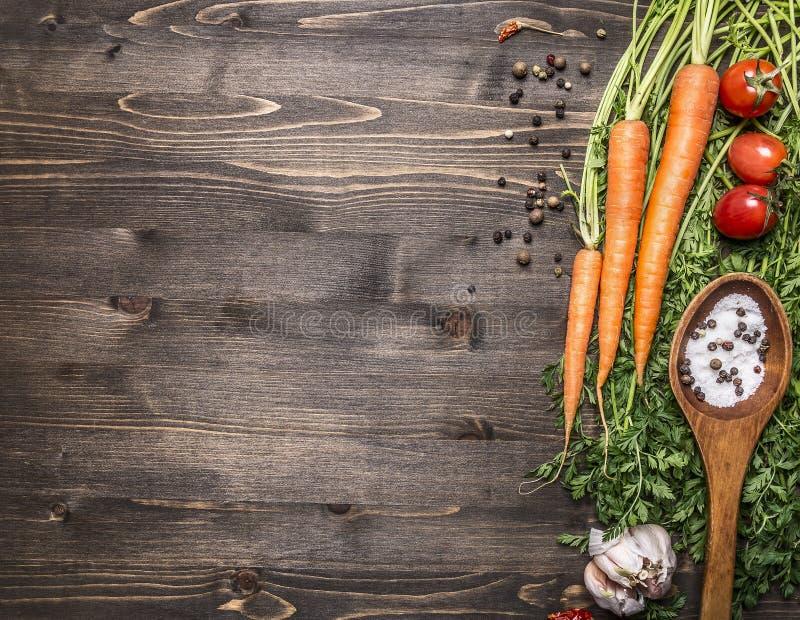 Frische Karotten mit Kirschtomaten, Knoblauch und hölzernes Löffelweinlesesalz und -pfeffer färbten ihn auf die hölzerne rustikal stockfotografie
