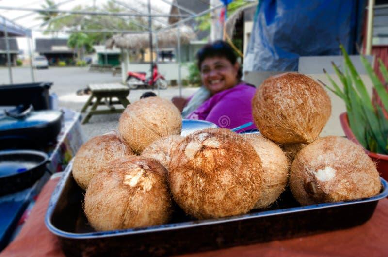 Frische Kokosnüsse des Koch-Islander-Frauenverkaufs lizenzfreies stockfoto