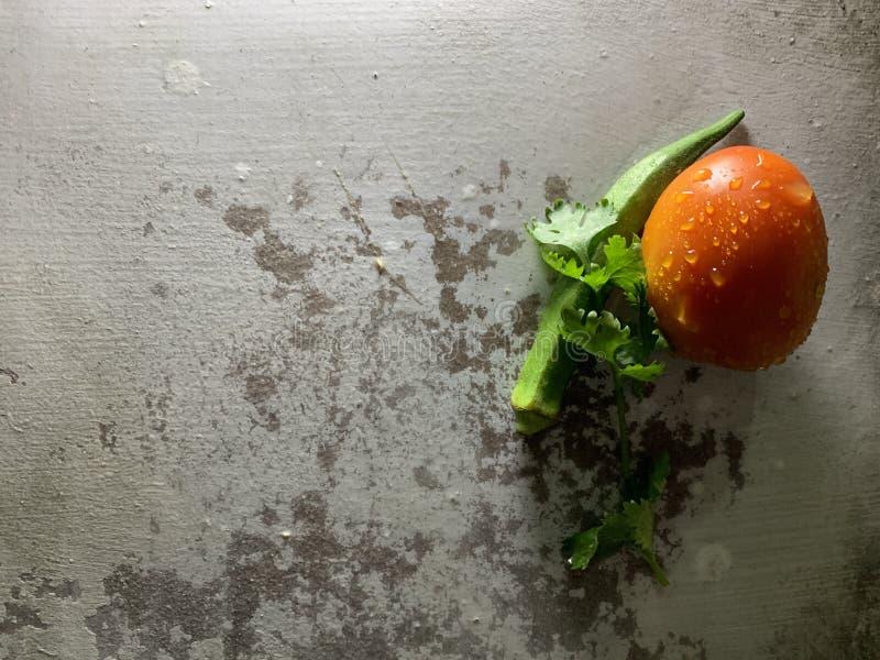 Frische Korianderblätter, grüner organischer essbarer Eibisch und rote Tomate mit Wassertropfen auf altem rustikalem Hintergrund stockfotos