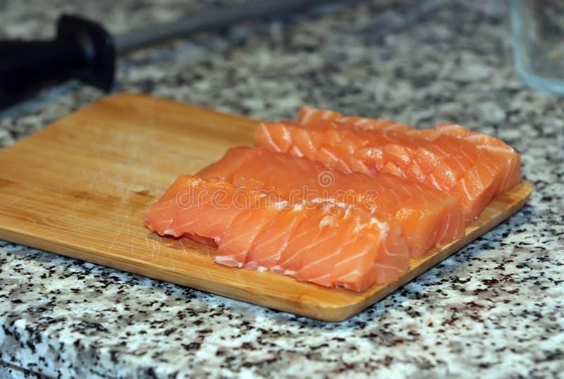 Frische Lachsfische mit Messer auf hölzernem kochendem Schreibtisch lizenzfreie stockfotos