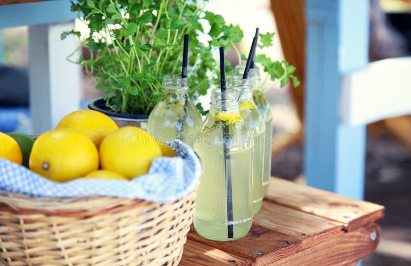 Frische Limonade und ein Korb mit Zitronen stockbild