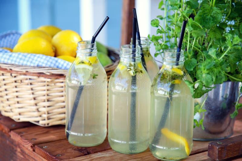 Frische Limonade und ein Korb mit Zitronen stockbilder