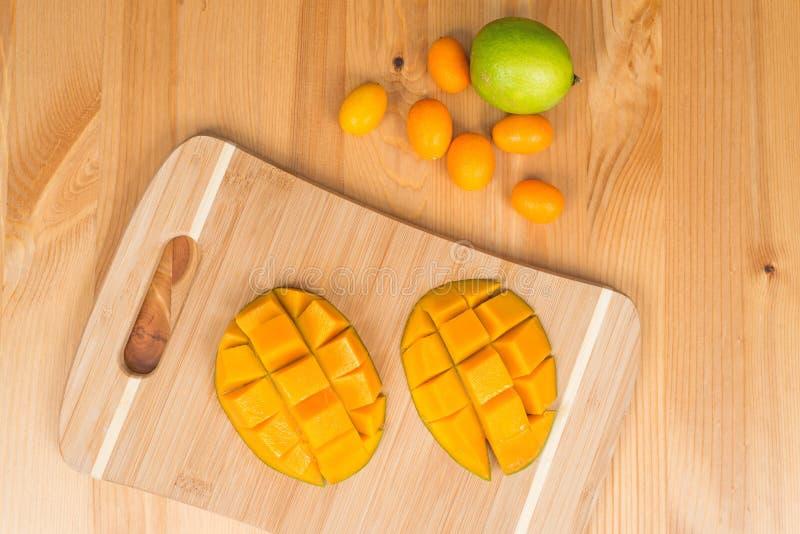 Frische Mango auf einem Schneidebrett mit frischen japanischen Orangen und einem Kalk, auf einem Holztisch lizenzfreie stockbilder