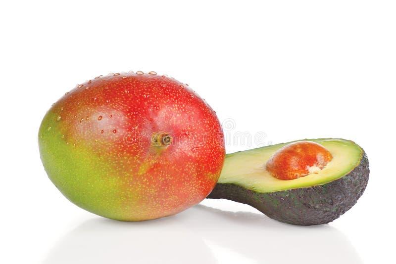 Frische Mangofrucht und Hälfte der Avocado lizenzfreies stockbild
