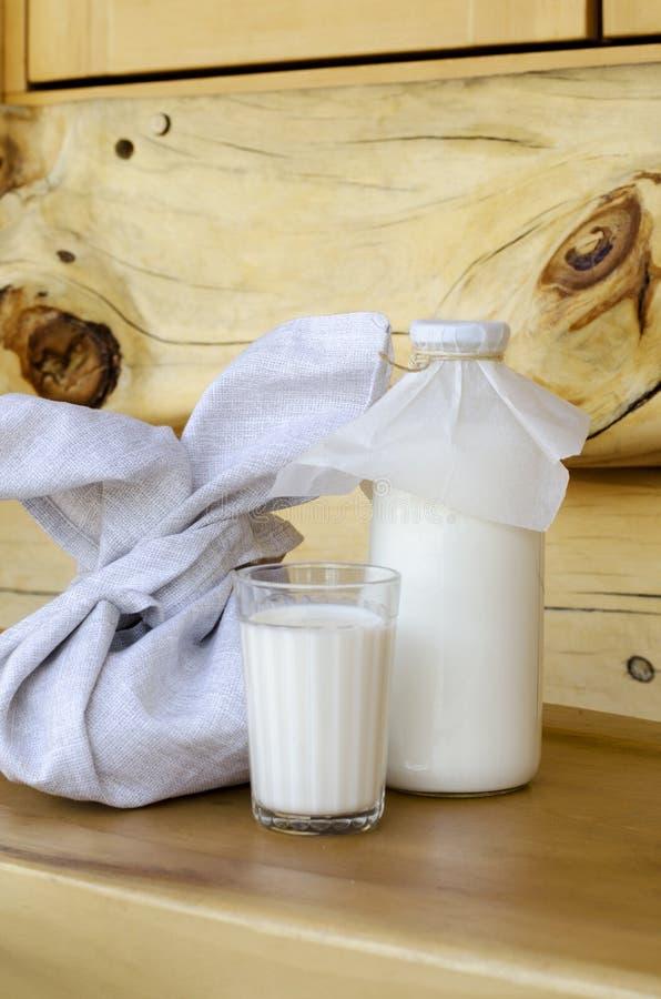 Frische Milch in einer Glasflasche und in einem Glas, nahe bei den Torten auf einem Holztisch Das Konzept von gesunden Bioprodukt lizenzfreie stockfotografie