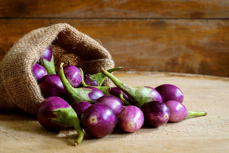 Frische mini purpurrote Aubergine im Hanfsack auf hölzernem Hintergrund lizenzfreie stockfotos