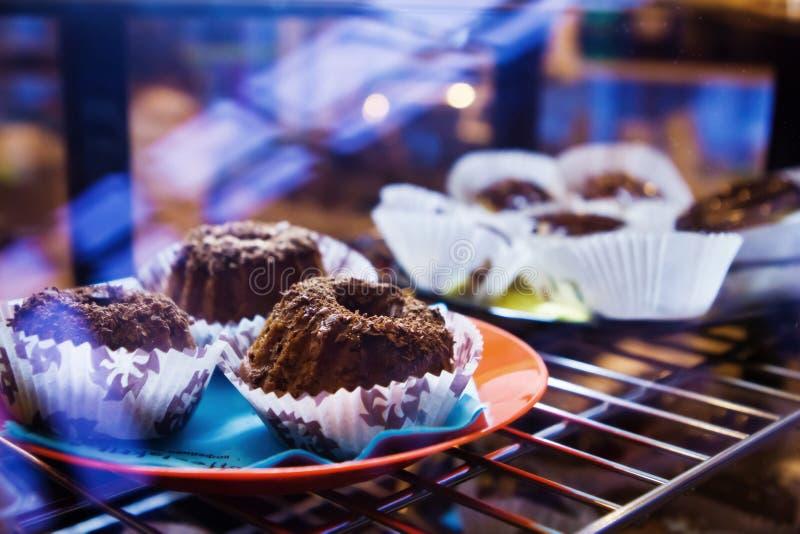Frische Muffins mit Schokoladensplittern in der Kühlschrankanzeige, süßes köstliches Lebensmittelfoto stockfoto