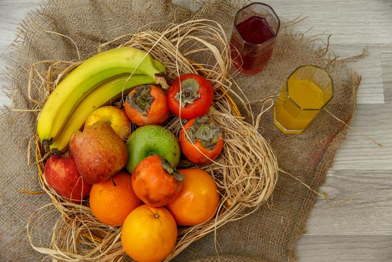 Frische natürliche Früchte in einem Strohkorb und frische Säfte auf einem Segeltuchhintergrund Das Konzept der natürlichen vegeta stockbild