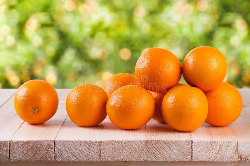Frische Orange auf Holz mit Unschärfe bokeh Hintergrund lizenzfreies stockbild