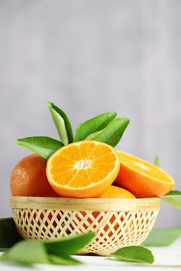 Frische Orangenfrucht im Korb auf weißem Tabellenhintergrund lizenzfreie stockfotografie