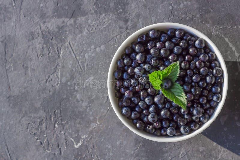 Frische organische Blaubeeren in einer Schüssel auf dunklem Hintergrund mit Kopienraum stockbilder