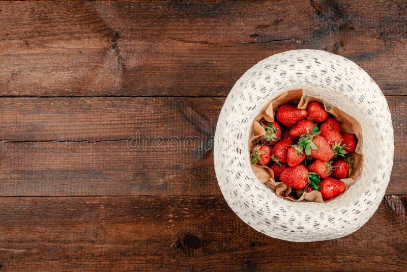 Frische organische Erdbeeren auf rundem Strohhut auf braunem rustikalem hölzernem Hintergrund Rote Beeren auf flacher Lage der Ta lizenzfreies stockbild