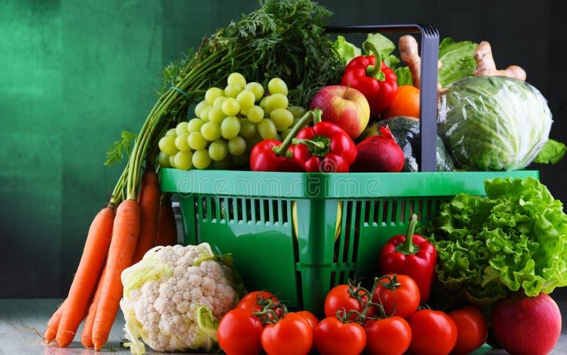 Frische organische Obst und Gemüse im Plastikeinkaufskorb lizenzfreie stockfotos