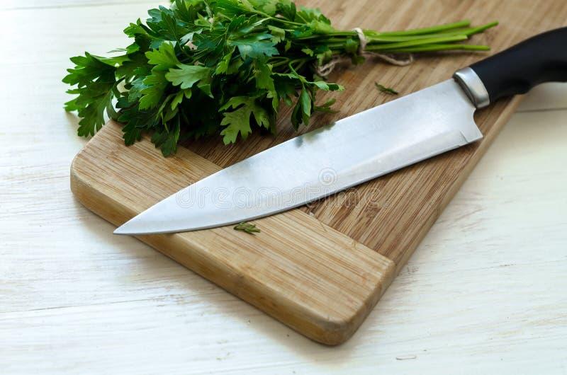 Frische organische Petersilie mit Messer auf hölzernem Schneidebrett stockbilder