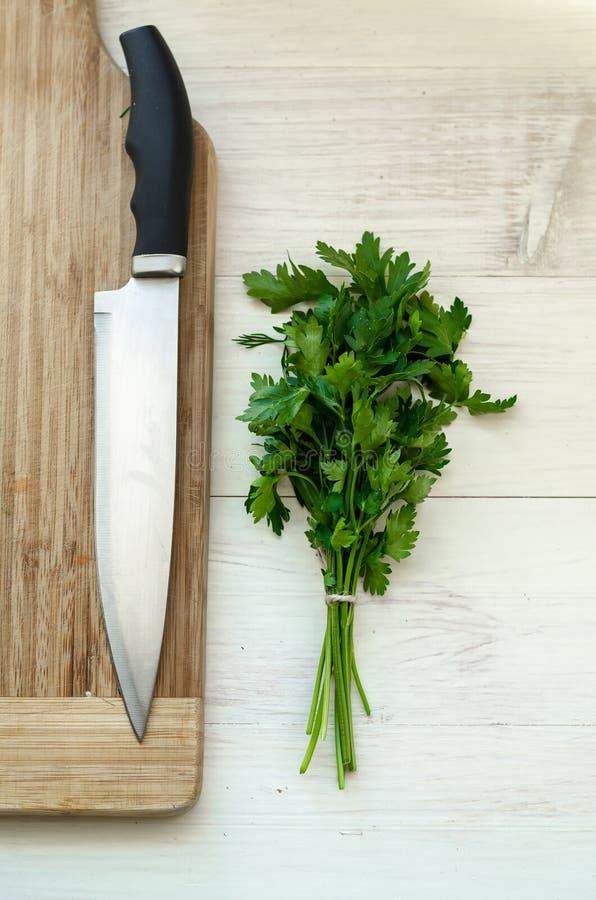Frische organische Petersilie mit Messer auf hölzernem Schneidebrett stockfotos