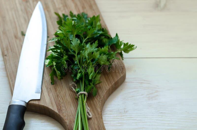 Frische organische Petersilie mit Messer auf hölzernem Schneidebrett lizenzfreie stockfotos