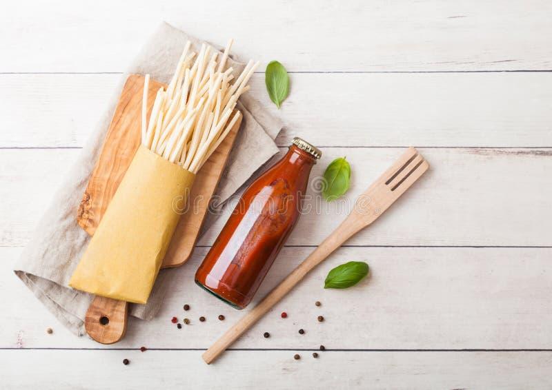 Frische organische selbst gemachte Spaghettiteigwaren mit Flasche der Tomatensauce und der hölzernen Spachtel und des Basilikumbl lizenzfreie stockfotos