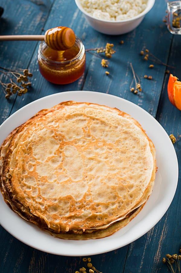 Frische Pfannkuchen mit Honig, Ahornsirup, Hüttenkäse und Tangerinen Hölzerner Hintergrund Beschneidungspfad eingeschlossen stockbild