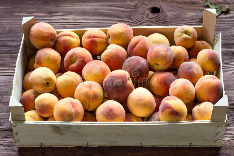 Frische Pfirsiche im hölzernen Kasten stockfotos