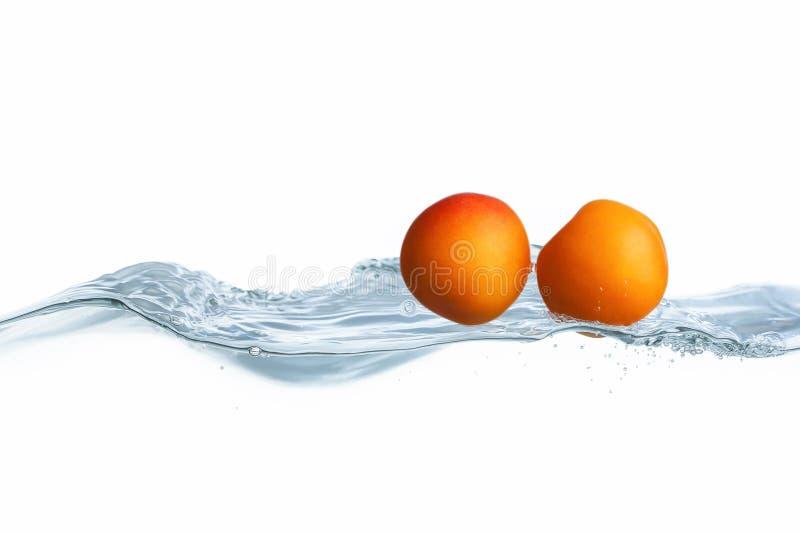 Frische reife Aprikose fiel in Wasserspritzen lizenzfreies stockfoto