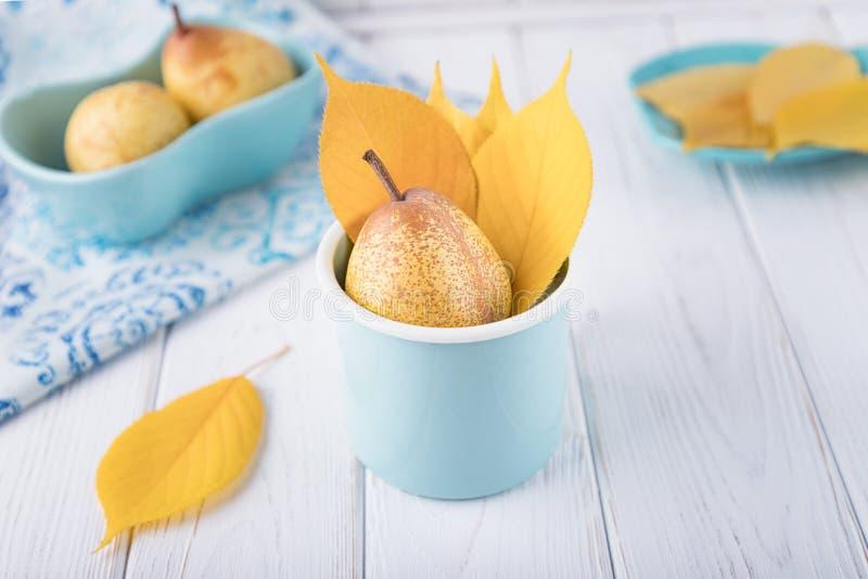 Frische reife Birne und gelber Herbstlaub in emaillierter Schale auf einem weißen Hintergrund Kopieren Sie Platz lizenzfreie stockbilder