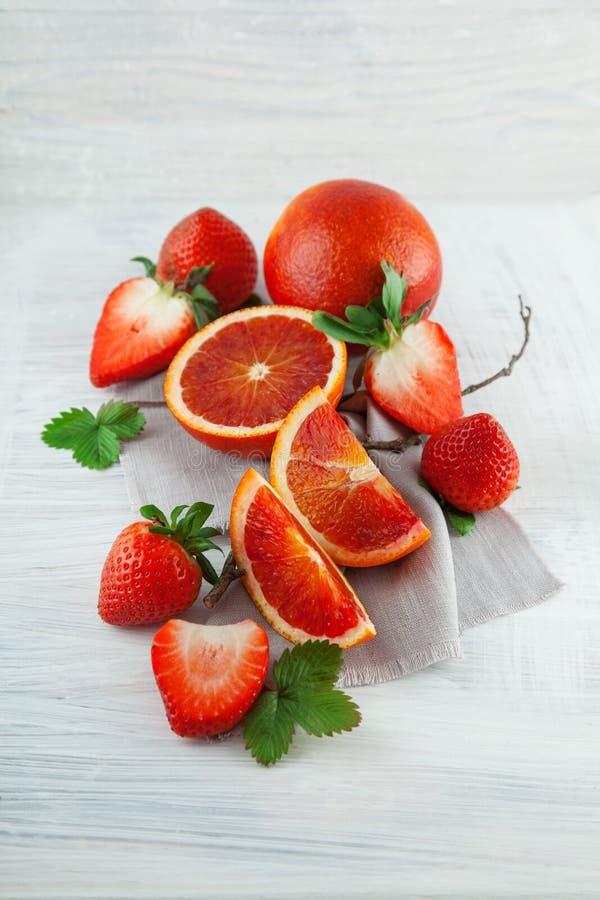 Frische reife Blutorangen und Erdbeeren, Scheiben, rustikale Lebensmittelphotographie auf weißer hölzerner Platte stockfotografie