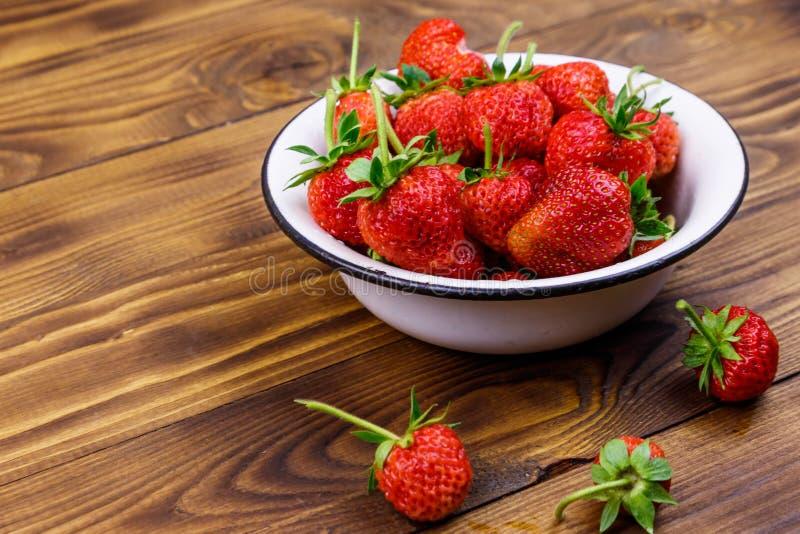 Frische reife Erdbeere in weißer Schüssel auf Holztisch lizenzfreie stockfotos