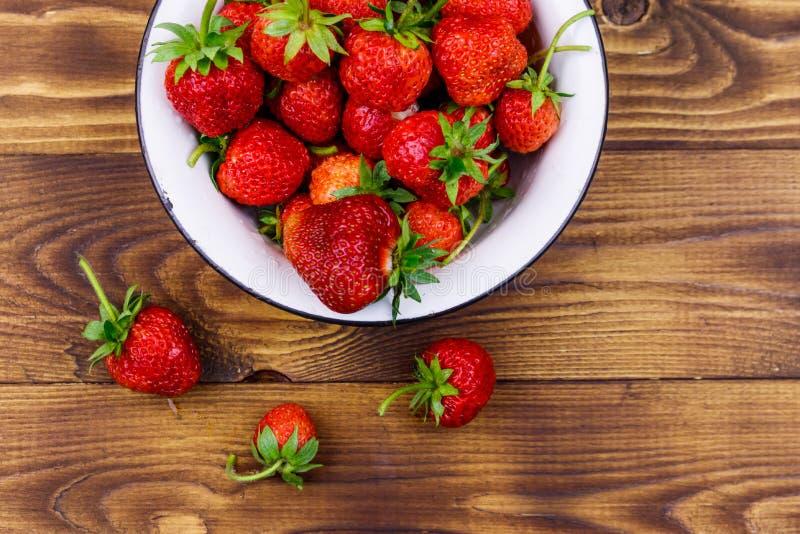 Frische reife Erdbeere in weißer Schüssel auf Holztisch Oberansicht stockfotos