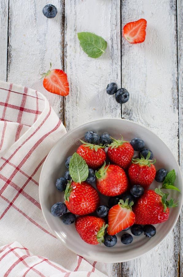 Frische reife Erdbeeren und Blaubeeren in einer Schüssel auf weißem woode lizenzfreie stockfotografie