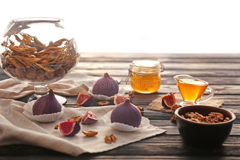 Frische reife Feigen mit Walnüssen und Honig auf Holztisch stockbilder