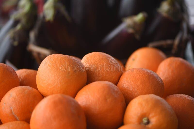 Frische reife Frucht von den Orangen oben angehäuft mit dunklem Hintergrund von Auberginen stockfotografie