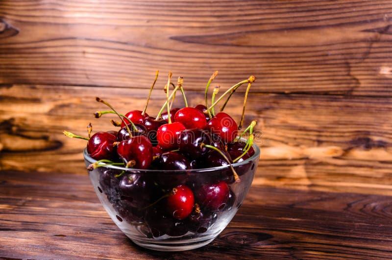 Frische reife Kirschen in der Glasschüssel auf Holztisch stockfotos